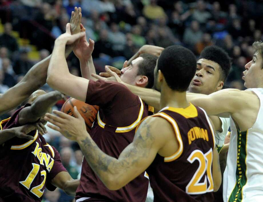 Siena and Iona players grasp for a rebound during the Siena Iona men's basketball game on Sunday, Jan. 12, 2014 in Albany, NY.   (Paul Buckowski / Times Union) Photo: Paul Buckowski / 00025111E