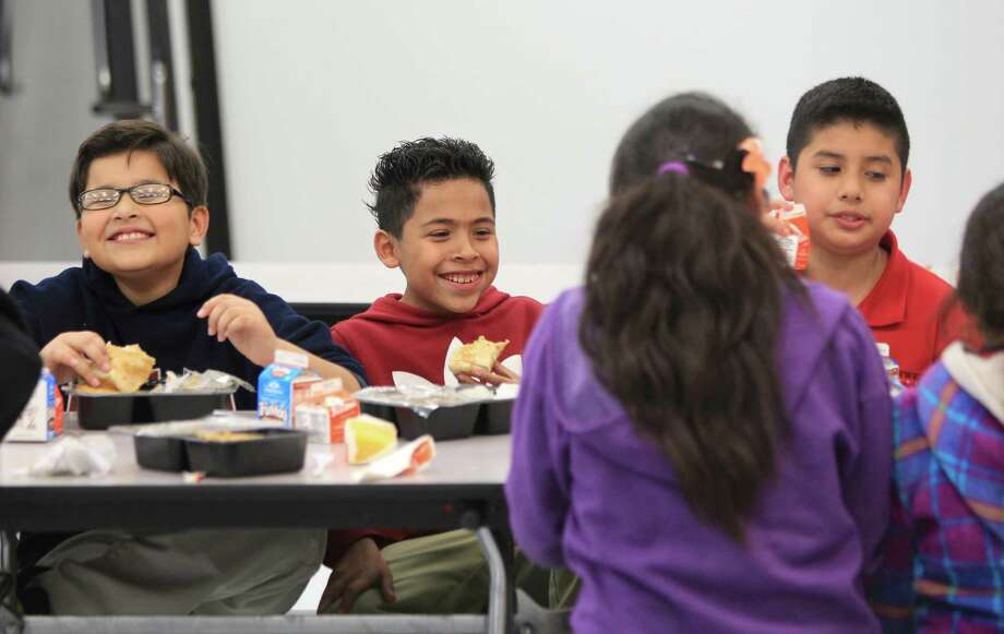 Jullyses Argueta, 10, Marcelo Gallegos, 11, and Raul Alfonso, 11, enjoy hot meals during the after-school program at Southwest Elementary-Bissonnet Campus. The campus is searching for more funding to keep the program open. Photo: Mayra Beltran, Staff / © 2013 Houston Chronicle