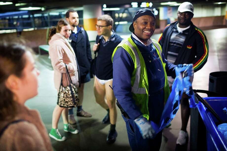 Michael Wooten, center right, of the Port of Seattle, chats with pants-free participants of the fifth annual No Pants Light Rail Ride Sunday, Jan. 12, 2014, from Seattle to SeaTac. Presented by Emerald City Improv, the event brought hundreds to ride the Central Link light rail, pretending nothing was different about their bottomless wardrobes than any other day of the year. Photo: JORDAN STEAD, SEATTLEPI.COM / SEATTLEPI.COM
