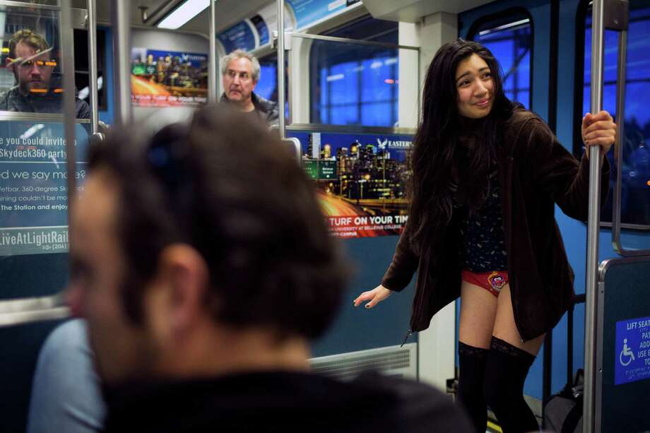 Nozomi Momo, right, sheds her trousers for the fifth annual No Pants Light Rail Ride Sunday, Jan. 12, 2014, from Seattle to SeaTac. Presented by Emerald City Improv, the event brought hundreds to ride the Central Link light rail, pretending nothing was different about their bottomless wardrobes than any other day of the year. Photo: JORDAN STEAD, SEATTLEPI.COM / SEATTLEPI.COM