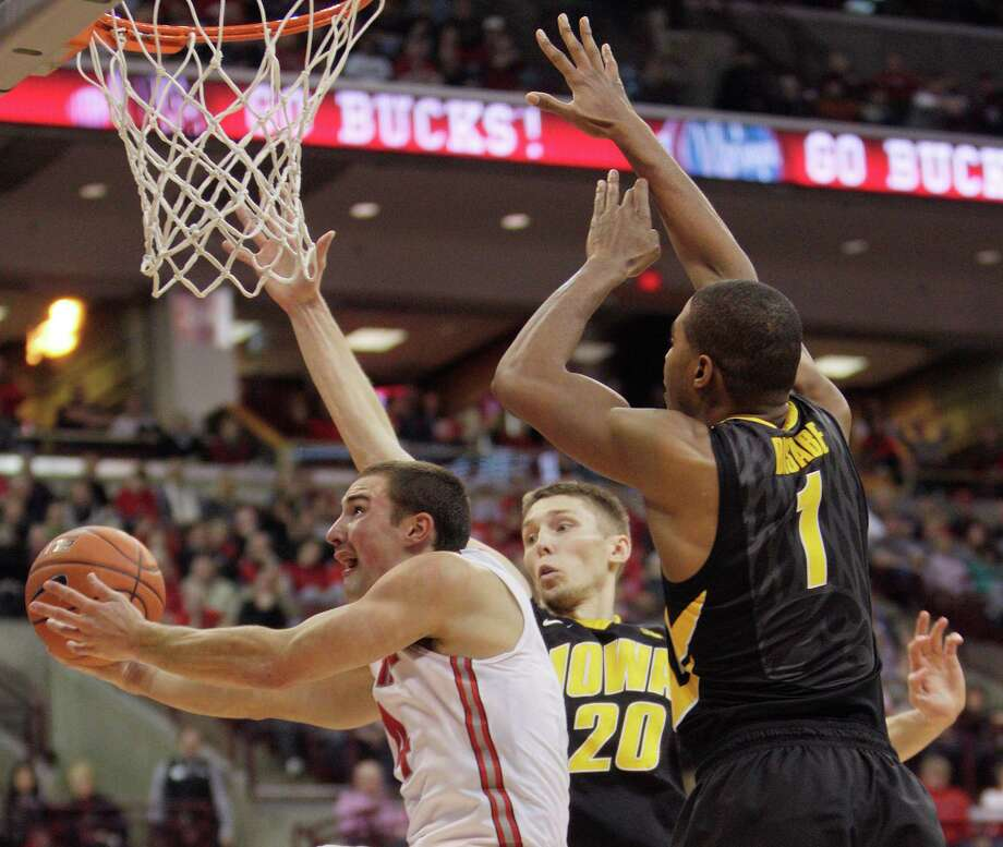 Aaron Craft, left, who had six of Ohio State's 17 turnovers, tries to squeeze between Iowa's Jarrod Uthoff, center, and Gabriel Olaseni. Photo: Jay LaPrete, FRE / FR52593 AP