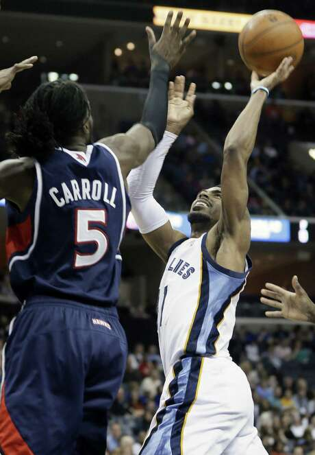 Grizzlies guard Mike Conley (right) shoots over the Hawks' DeMarre Carroll en route to his 21 points. Photo: Associated Press / AP