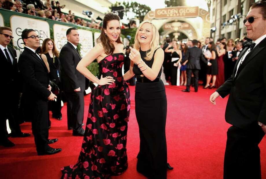 Tina Fey, left, and Amy Poehler, hosts of the 71st Annual Golden Globe Awards, cut up on the red carpet outside the Beverly Hilton Hotel in Beverly Hills, Calif. Photo: Christopher Polk/NBC, Contributor / 2014 Christopher Polk/NBC