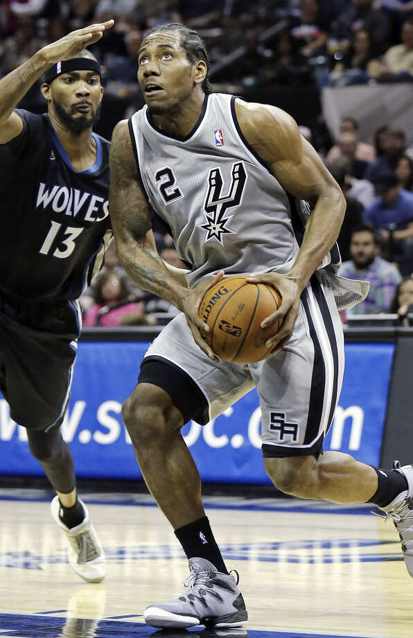 Forward Kawhi Leonard drives around Minnesota's Corey Brewer. Leonard led the Spurs with 17 points. Photo: Edward A. Ornelas / Express-News / © 2014 San Antonio Express-News