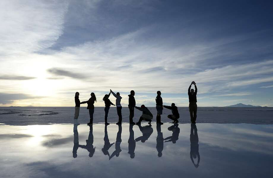 Tourists pose at the Salar de Uyuni, the world's largest salt flat, near the crest of the Andes near 