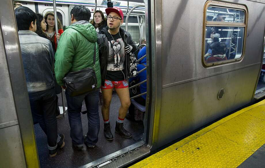 A participant not wearing pants stands aboard a departing subway train, taking part in the annual No Pants Subway Ride Sunday, Jan. 12, 2014, in New York. The improv event invites people onto the subways without pants to act out what might be a normal commute. (AP Photo/Craig Ruttle) Photo: Craig Ruttle, Associated Press