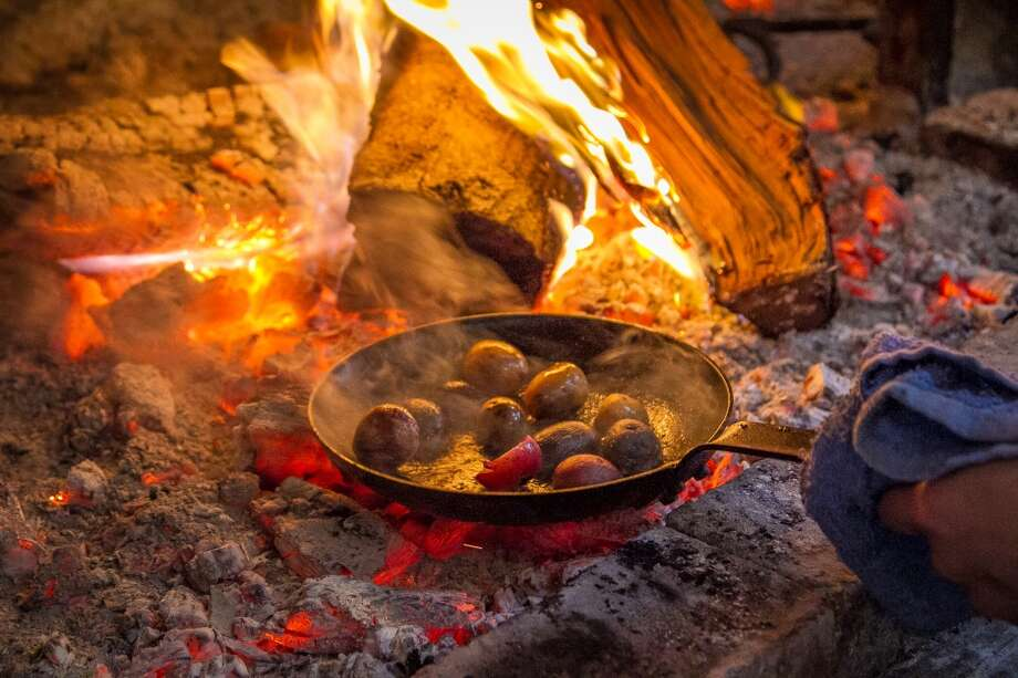 Potatoes cook in the fire at TBD. Photo: John Storey, Special To The Chronicle