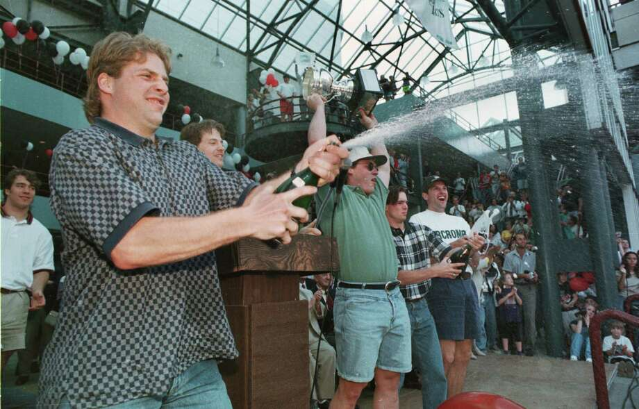 Matt Ruchty holds the Calder Cup high above his head on March 30, 1995 while his Albany River Rats teammates, left to right, Scott Pellerin, Kevin Dean, Steve Sullivan and Bill Armstrong help with the champagne duties during Tuesday's celebration at Knickerbocker Arena. Photo: TOM LAPOINT, DG / ALBANY TIMES UNION