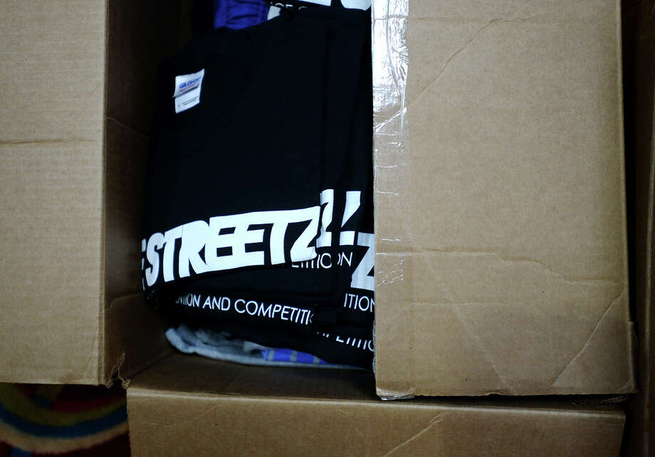 "Tee-shirts for sale sit in boxes near the registration desk for the Streetz Dance Convention and Competition on Friday afternoon. A small crew began the set up for the weekend's events at the Holiday Inn and Suites on Friday afternoon. The event will be drawing more than 400 participants to learn and dance under a variety of teachers, including organizer and Port Neches resident Ty Riley. Other instructors include Alex Anderson, Daniel Baker, and Kameron Bink, all of ""So You Think You Can Dance"" fame, among others. The event began in 2009, and has grown from single venues to multiple conventions in three cities. Photo taken Friday, 1/10/14 Jake Daniels/@JakeD_in_SETX Photo: Jake Daniels / ©2013 The Beaumont Enterprise/Jake Daniels"