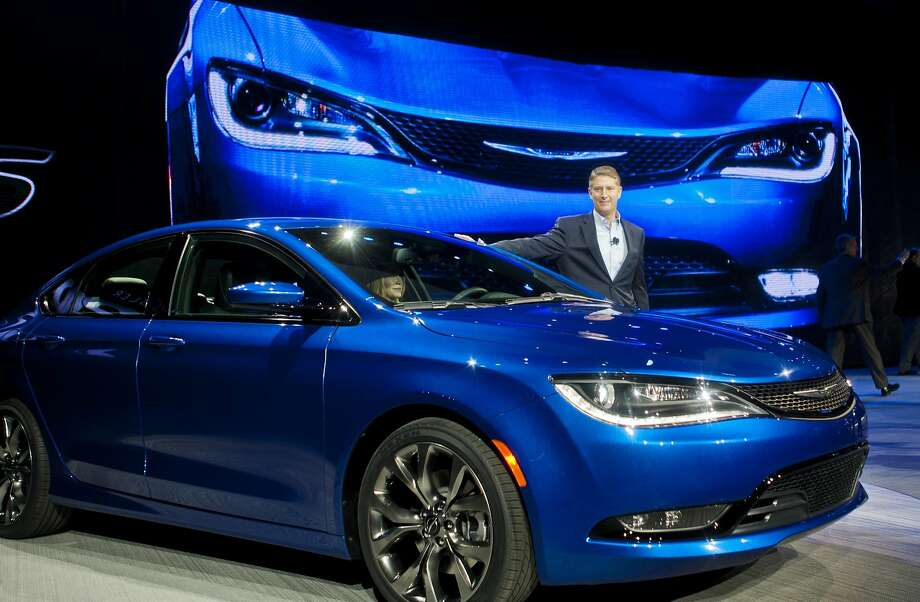 Chrysler President and CEO Al Gardner poses with a newly unveiled 2015 Chrysler 200 sedan. Photo: Tony Ding, Associated Press