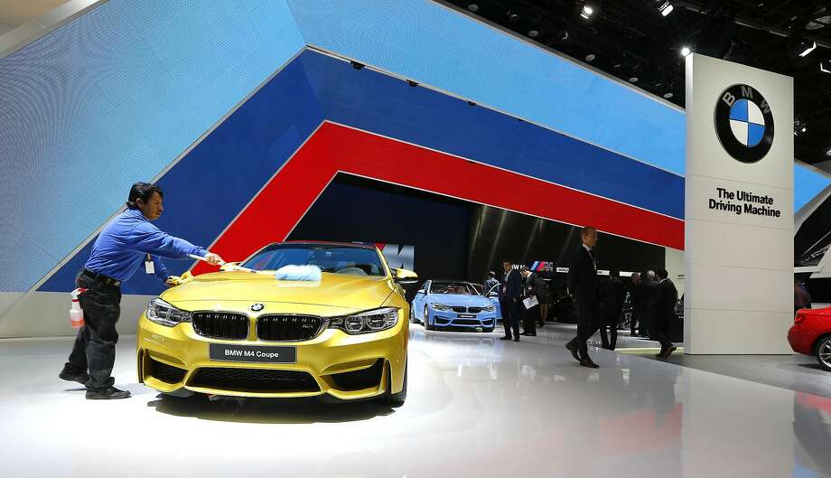 A BMW M4 Coupe is cleaned during media previews at the North American International Auto Show. Photo: Paul Sancya, Associated Press