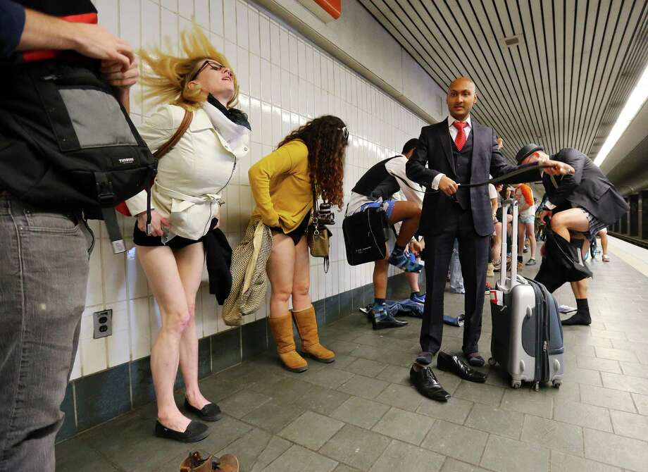 Participants begin to shed their pants for the No Pants Subway Ride annual event joining other pantless riders invading MARTA at the Civic Center station on Sunday, Jan. 12, 2014, in Atlanta. The staged event was organized by the group Impro Everywhere. (AP Photo/Atlanta Journal-Constitution, Curtis Compton)  Photo: Curtis Compton, AP / Atlanta Journal & Constitution