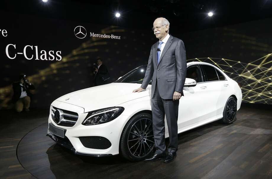 Dr. Dieter Zetsche, chairman of the board of management Daimler AG and Head of Mercedes-Benz Cars stands next to the automaker's new C-Class car during a preview night for the North American International Auto Show. Photo: Carlos Osorio, Associated Press