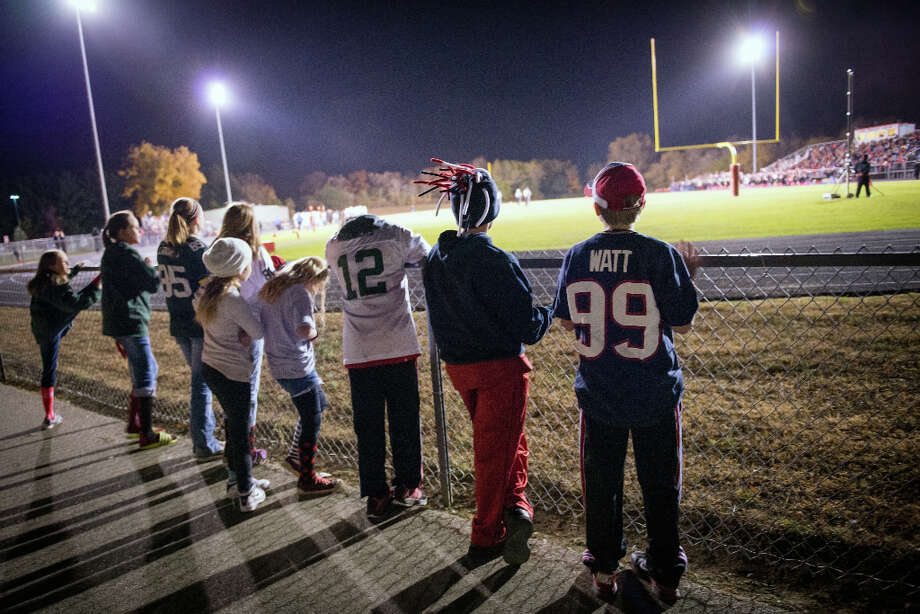 Luke Locher, 11, wears the #99 jersey of Houston Texans defensive end J.J. Watt, as he watches the homecoming football game of the Pewaukee Pirates, Watt's high school alma mater, on Friday, Oct. 5, 2012, in Pewaukee,Wis. Photo: Smiley N. Pool, Houston Chronicle / © 2012  Houston Chronicle