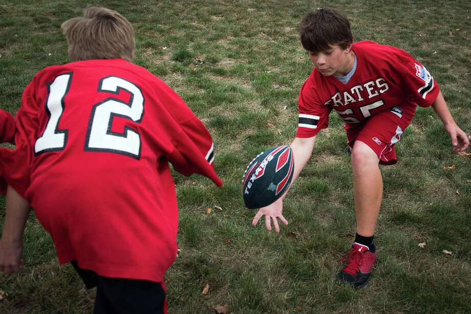 While the football pride of Pewaukee, Wis. will always be the hometown Pewaukee Pirates, evidence of the growing influence of the Houston Texans can be seen in the choice of the ball for a front yard game of catch between Luke Lochner, 11, left, and Drew Retherford, 12, who live in the same neighborhood as the family home of Houston Texans defensive end J.J. Watt. Photo: Smiley N. Pool, Houston Chronicle / © 2012  Houston Chronicle