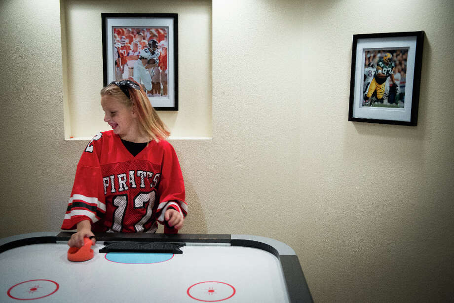 Beneath photos showing Green Bay Packers Hall of Fame defensive lineman Reggie White, right, and Houston Texans defensive end J.J. Watt during his playing days as a tight end at Central Michigan University, neighbor Morgan Goodman plays air hockey in the basement of the Watt family home in Pewaukee,Wis. Photo: Smiley N. Pool, Houston Chronicle / © 2012  Houston Chronicle