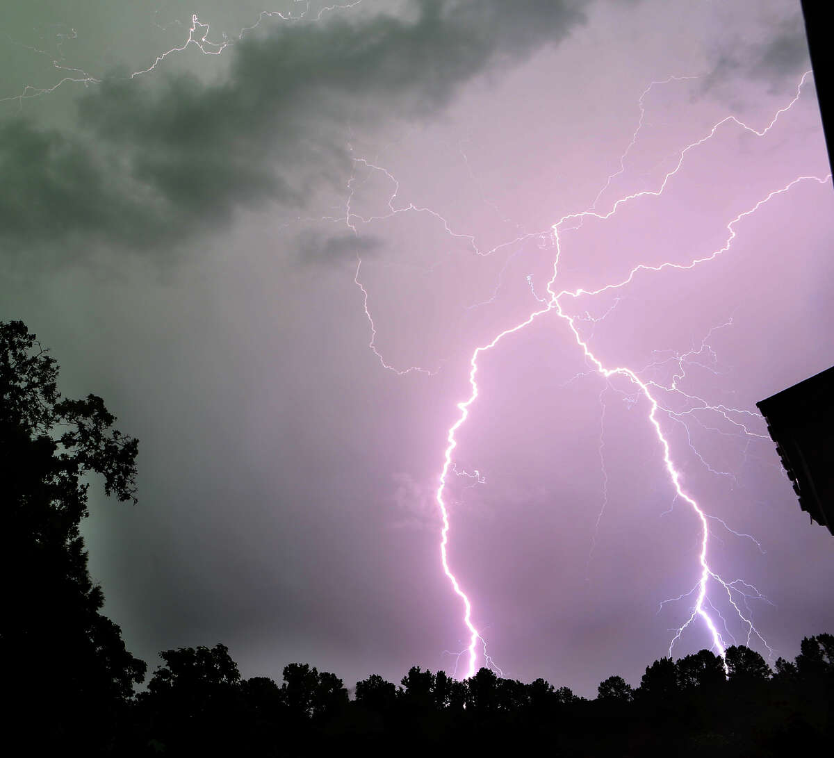A pair of lightning bolts are seen striking the ground as a line of thunderstorms passes over Tyler, Texas on Tuesday, May 22, 2013.