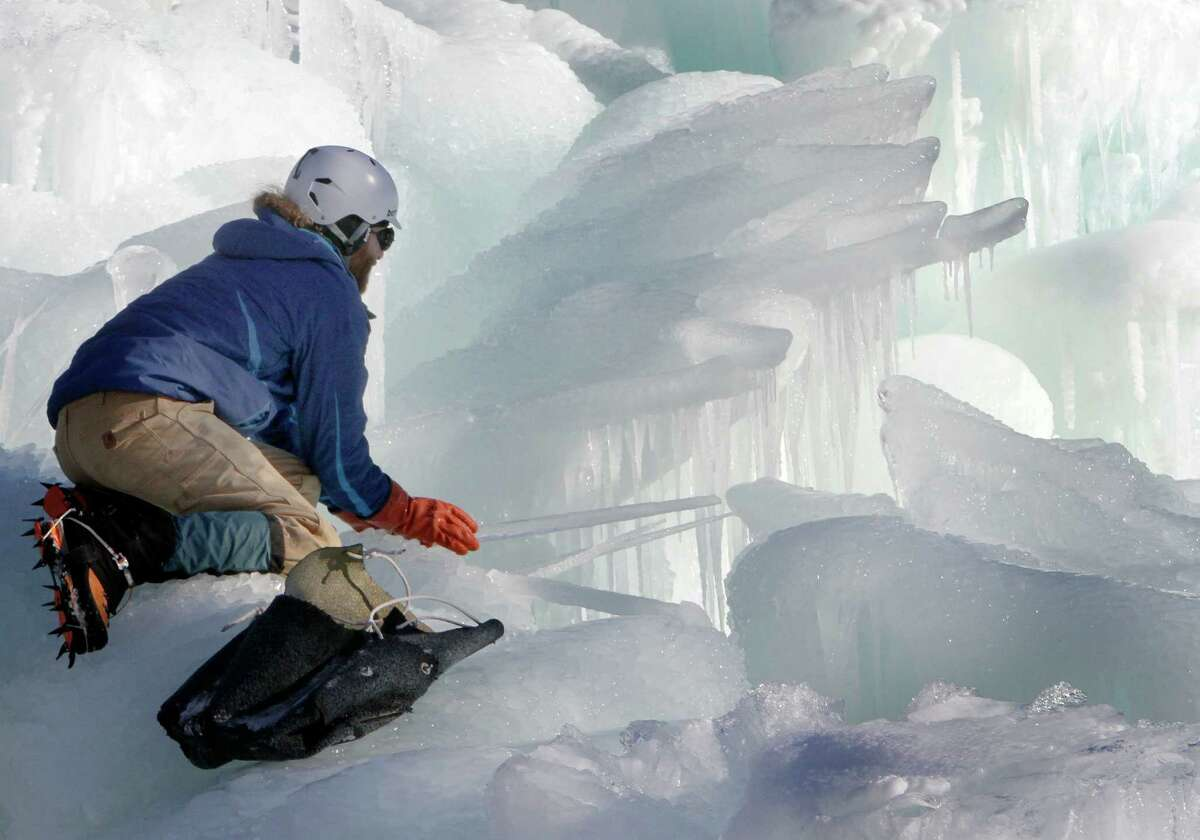 In this Wednesday, Jan. 8, 2014 photo, Cory Livingood places icicles on the top of his ice castle at the base of the Loon Mountain ski resort in Lincoln, N.H. The ice castle begins to grow in the fall when the weather gets below freezing and thousands of icicles are made and harvested then placed around sprinkler heads and sprayed with water. The castle will continue to grow as long as the temperatures stay below freezing. (AP Photo/Jim Cole) ORG XMIT: CON301