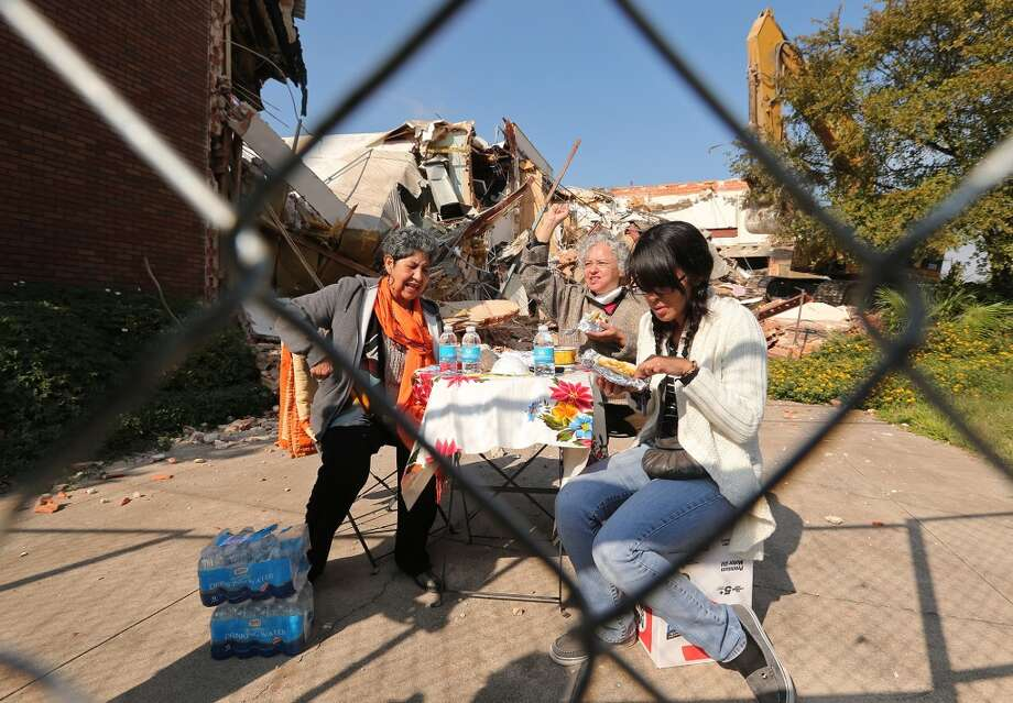 Protesters Antonia Castañeda (from left), Graciela I. Sanchez and Amy Manor sets up a lunch table while attempting in protest of the demolition of the Univision building. Photo: Jerry Lara, Express-News