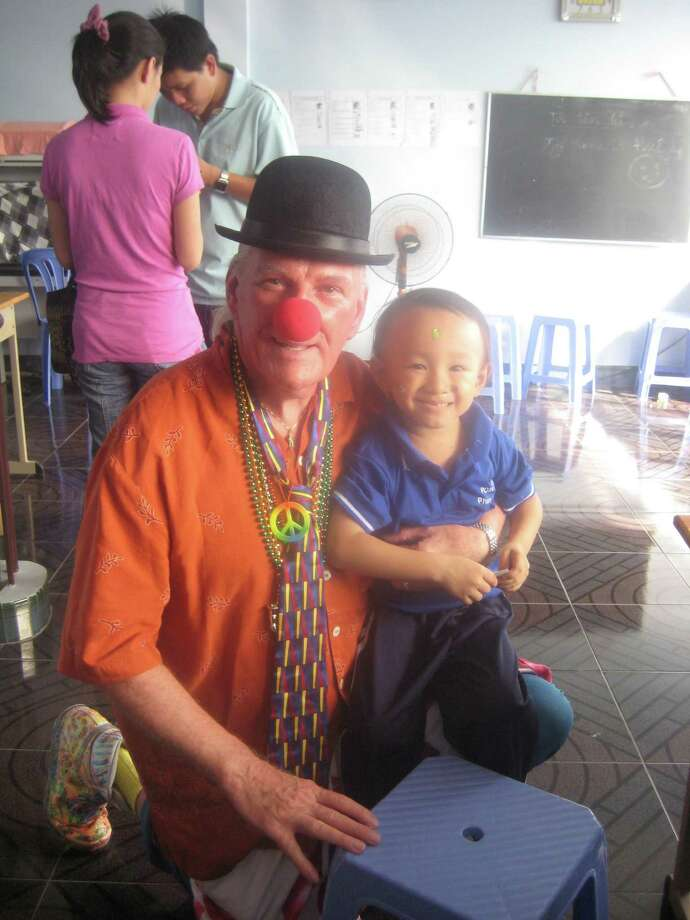 Gerard Brooker is seen here visiting with an orphan in Vietnam. Brooker has traveled to more than 100 countries to raise awareness about the plight of children who are hungry, or who have suffered because of wars or other tragic circumstances. When called upon, he uses the art of clowning to bring some joy to these children. Photo: Contributed Photo / The News-Times Contributed