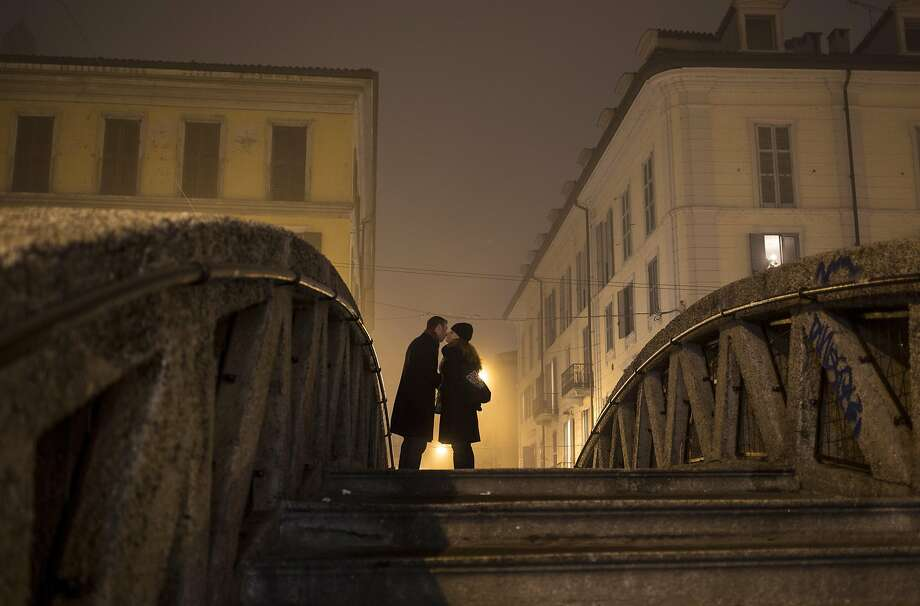 That's amore:A young couple kiss on a bridge over the Naviglio Grande channel during a foggy evening in Milan. Photo: Alexander Zemlianichenko, Associated Press
