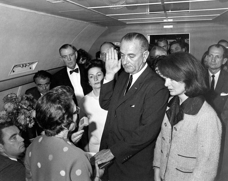 Judge Sarah T. Hughes administers the Presidential Oath of Office to Lyndon Baines Johnson around 2:40 p.m. (CT) aboard Air Force One at Love Field in Dallas. Mrs. Johnson, Mrs. Kennedy, Jack Valenti, Rep. Albert Thomas, Rep. Jack Brooks, Associate Press Secretary Malcolm Kilduff (holding microphone) and others witness the oath. Photo: Handout, MCT / MCT