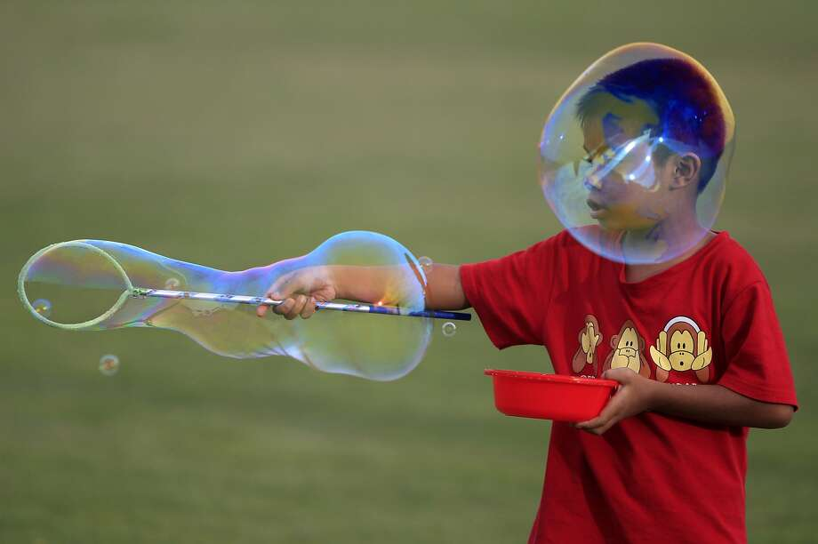 Blow-back:Those who create giant bubbles sometimes become engulfed by giant bubbles. (Kuala Lumpur.) Photo: Lai Seng Sin, Associated Press
