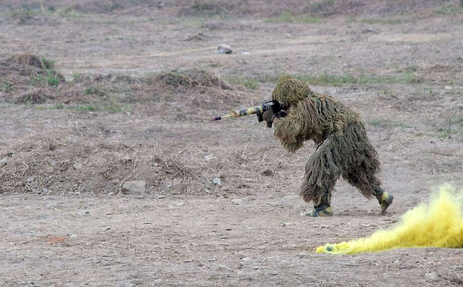 Poor use of camouflage: A rifle-wielding bush fools no one at a combat skills demonstration in southern Pingtung, Taiwan. Photo: Sam Yeh, AFP/Getty Images