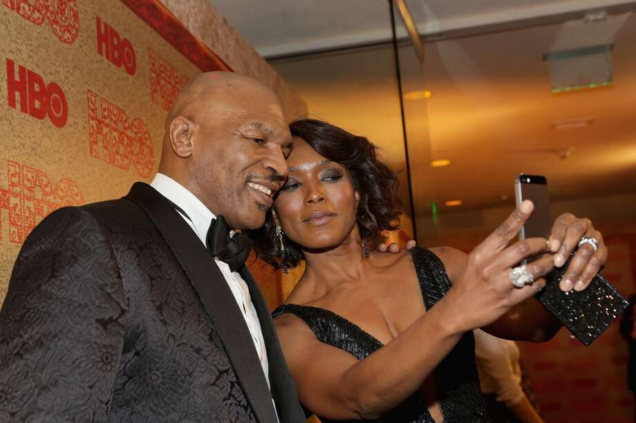 Former boxer Mike Tyson (L) and actress Angela Bassett attend HBO's Post 2014 Golden Globe Awards Party held at Circa 55 Restaurant on January 12, 2014 in Los Angeles, California. Photo: Mike Windle, Getty Images