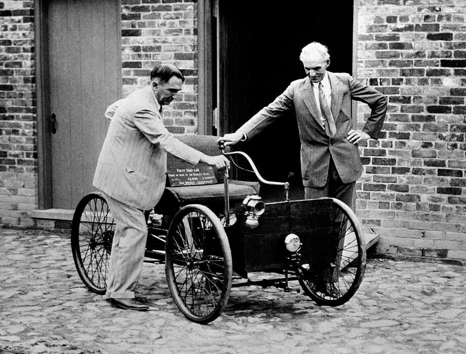 Henry Ford, right, stands with his first car built in 1892, assembled in the brick barn in the background in Detroit. At left is James Bishop. Photo: Uncredited / AP