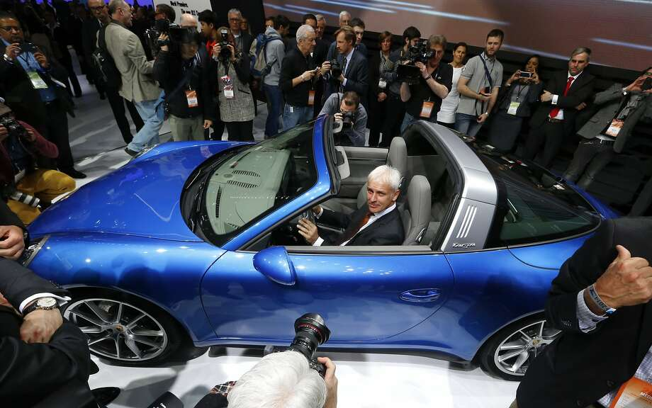 Matthias Muller, President and CEO, Porsche AG poses in the Porsche 911 Targa during media previews during the North American International Auto Show. Photo: Paul Sancya, Associated Press