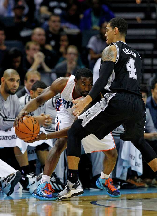 Charlotte Bobcats' Michael Kidd-Gilchrist, left, tries to drive against San Antonio Spurs' Danny Green, right, during the first half of an NBA basketball game in Charlotte, N.C., Saturday, Dec. 8, 2012. Photo: Chuck Burton, Associated Press / AP
