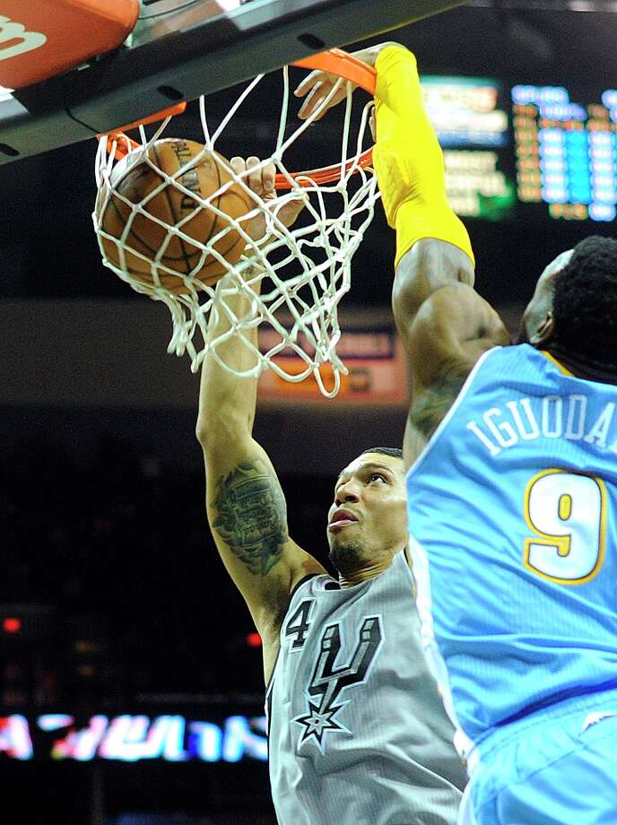Danny Green of the San Antonio Spurs dunks as Andre Iguodala of the Denver Nuggets defends during first-quarter NBA action in the Alamodome on Nov. 17, 2012. Photo: Billy Calzada, San Antonio Express-News / SAN ANTONIO EXPRESS-NEWS