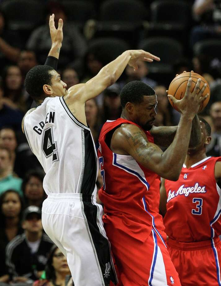 Spurs' Danny Green (4) attempts to swat the ball away from Los Angeles Clippers' DeAndre Jordan (06) in the first half of their game at the AT&T Center on Monday, Nov. 19, 2012. Photo: Kin Man Hui, San Antonio Express-News / © 2012 San Antonio Express-News