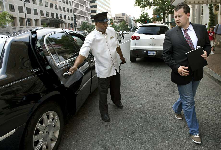 WASHINGTON, DC  - JULY 16: (L-R) Hotel employee Tedros Birat opens the Uber Car door for Brendan Kownacki who uses the UBER car via a smartphone app to get around town rather than cabs in Washington, DC on July 16, 2012.  He pays a little more than cabs but says it's worth it.  It's automatically billed to his credit card, tip included, and the quality of the cars and drivers leaves no surprises for him or his clients.  (Photo by Linda Davidson / The Washington Post via Getty Images) Photo: The Washington Post, The Washington Post/Getty Images