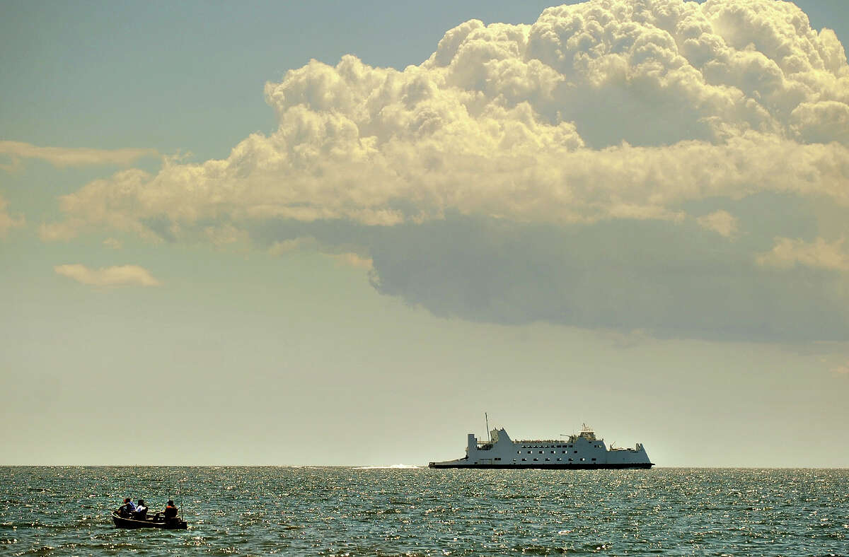 A trio of fishermen and the Port Jefferson ferry share the Sound under billowy clouds off Seaside Park in Bridgeport, Conn. on Tuesday, August 6, 2013.