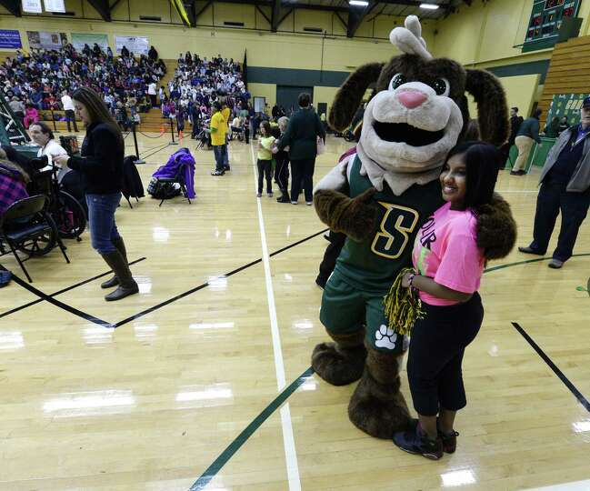 Allison Mahabier, 12, of the Zoller School of Schenectady,gets a hug from the Siena mascot Monday af