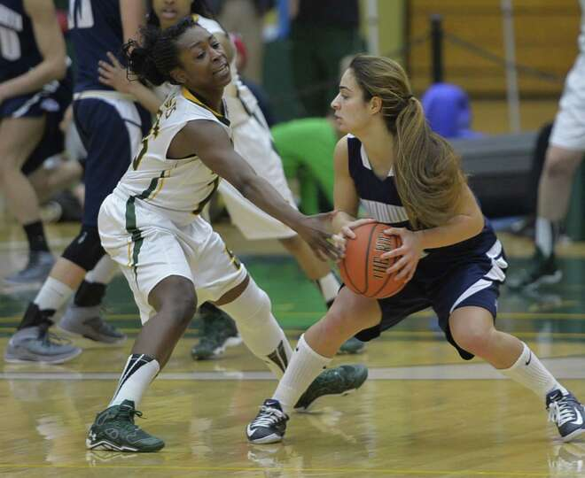 Siena's Tehresa Coles, left, reaches in for the ball against a Monmouth player while playing before