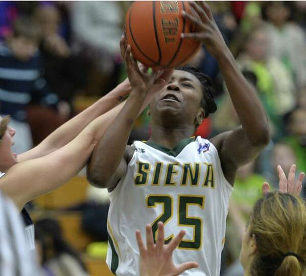 Siena's Tehresa Coles is swarmed by Monmouth defenders before a crowd of approximately 1,500 grade s