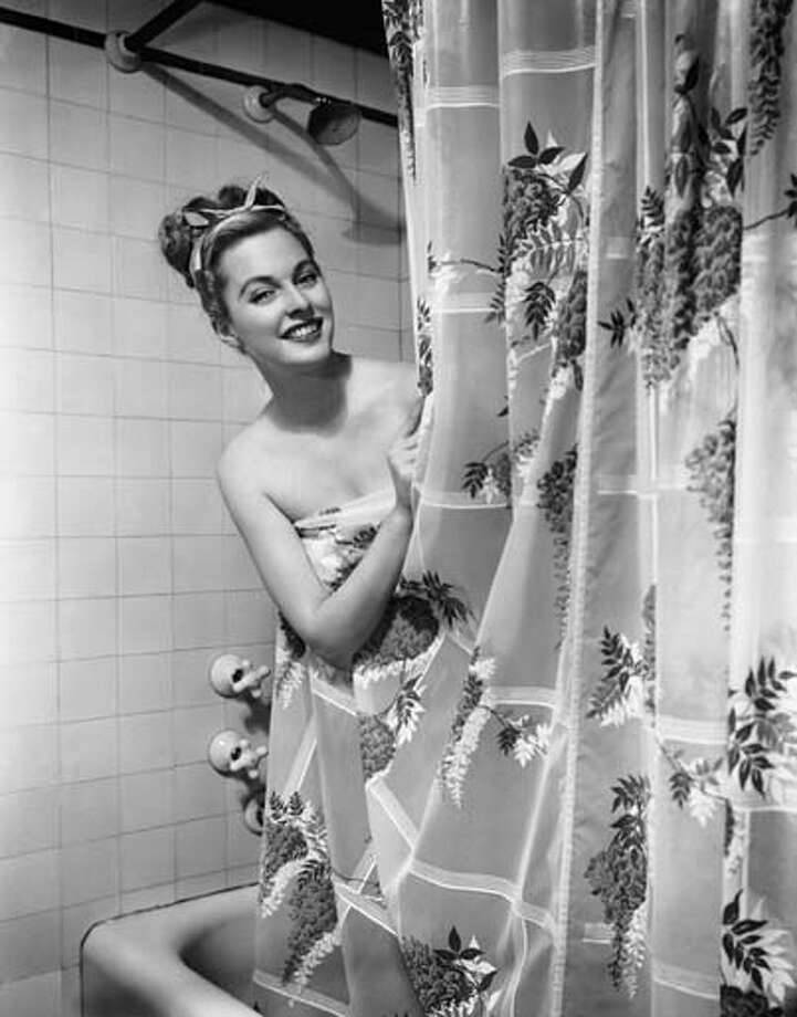 Woman taking shower, circa 1950s. Photo: George Marks, Getty Images / Hulton Archive