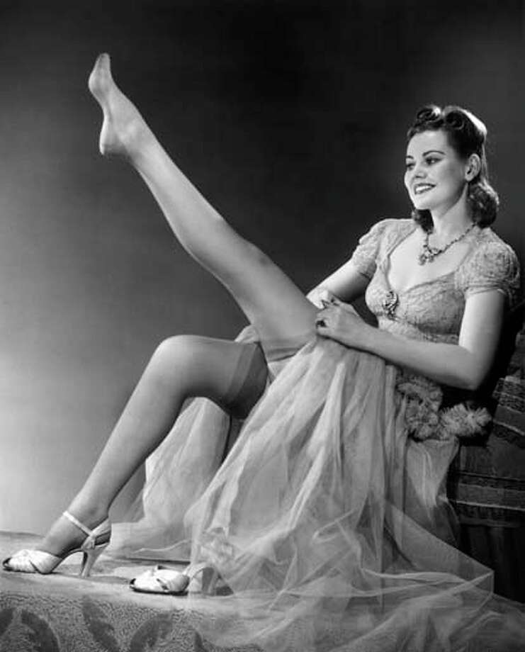Woman in evening wear pulling on silk stockings, circa 1950s. Photo: George Marks, Retrofile/Getty Images / Retrofile