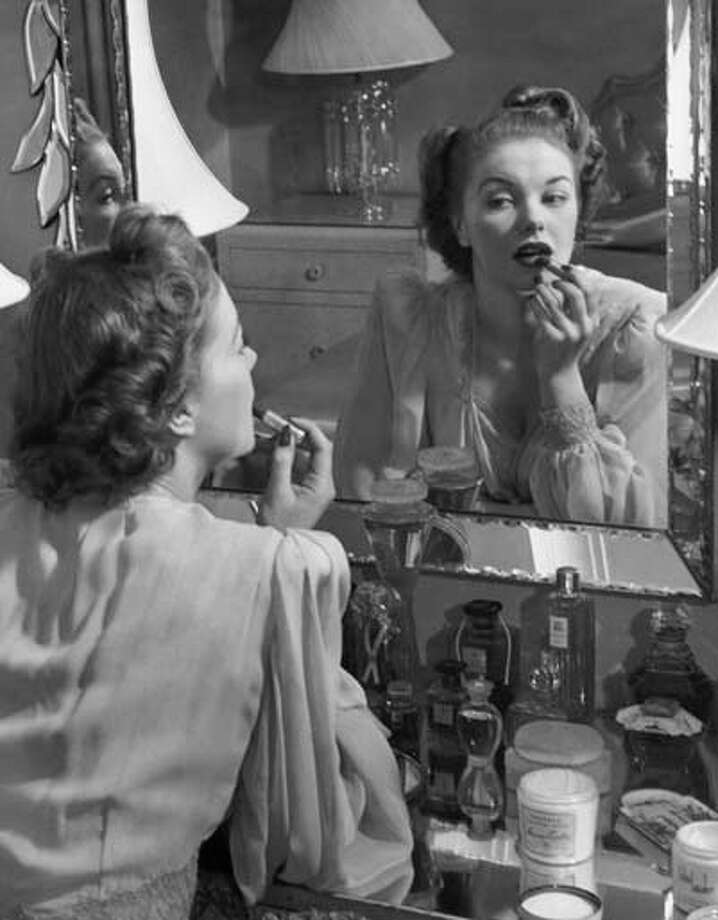 Woman applying lip-stick in front of mirror, circa 1950s. Photo: George Marks, Retrofile/Getty Images / Retrofile