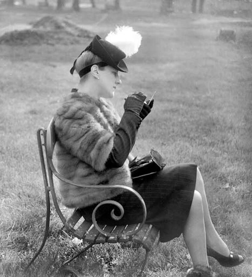Mrs Phillip Worthington reapplies her makeup in England's Hyde Park, wearing a fur and powder-puff hat, October 1941. Photo: Planet News Archive, SSPL Via Getty Images / SSPL/Planet News Archive