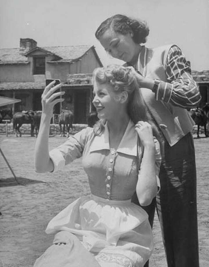 Actress Arlene Dahl (C) getting her hair fixed by a stylist while on location shooting the movie  Ambush, circa 1950s. Photo: Alfred Eisenstaedt, Time & Life Pictures/Getty Image / Time Life Pictures