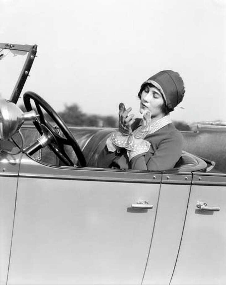 An American woman primps while behind the wheel of a car. Some things never change. Photo: H. Armstrong Roberts, Retrofile/Getty Images / Retrofile
