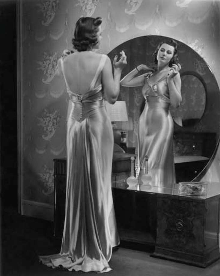 Woman wearing dress looking in mirror, circa 1950s. Photo: George Marks, Retrofile/Getty Images / Retrofile