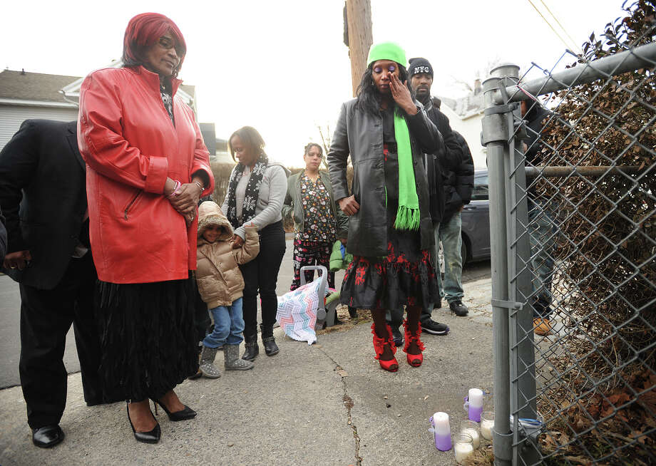 Sarah Abraham, left, and Melissa Gibbs, right, grandmother and mother of Brian Stukes, stand in prayer after lighting candles at the spot on Coleman Street in Bridgeport, Conn. where Stukes died after being shot by Bridgeport police on April 1, 2013. Photo: Brian A. Pounds / Connecticut Post