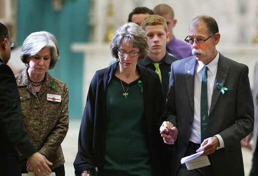 Mickey Redus, right, walks with his wife Valerie Redus, and one of their sons Ethan Redus, center, as they leave The University of the Incarnate Word memorial service for Robert Cameron Redus, the student fatally shot by a UIW officer, Monday, Jan. 13, 2013. Sharon Welkey, left, the Dean of School of Media and Design, and one of Robert Cameron Redus's teachers, escorts the family members. Photo: BOB OWEN, San Antonio Express-News / © 2012 San Antonio Express-News