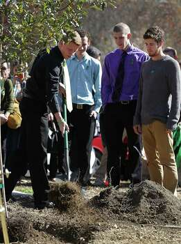Ethan Redus, left, brother of slain University of the Incarnate Word student Robert Cameron Redus, shovels dirt on a tree planted in Cameron's honor on campus. The school held a memorial service for Robert Cameron Redus, the student fatally shot by a UIW officer, Monday, Jan. 13, 2013. Cameron's other brothers, left to right, Kris Redus, William Redus, and Everett Redus also took a turn planting the tree. Photo: BOB OWEN, San Antonio Express-News / © 2012 San Antonio Express-News