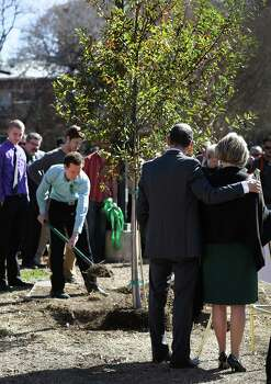 Mickey Redus comforts his wife Valerie Redus, as their sons help plant a tree in memory of their brother Robert Cameron Redus, the University of the Incarnate Word student that was fatally shot by a UIW officer, Monday, Jan. 13, 2013.  The school held a prayer service for Robert Cameron Redus. Photo: BOB OWEN, San Antonio Express-News / © 2012 San Antonio Express-News